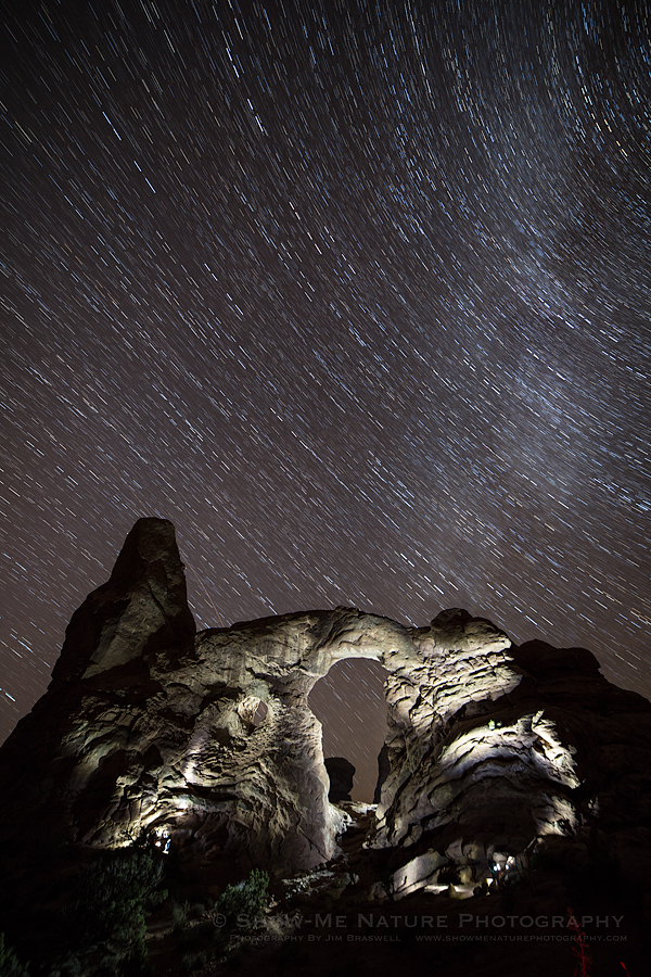 Star trails over Turret Arch, with the arch painted in light